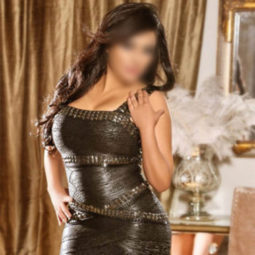 Escort Esmeralda is wearing black leather dress standing by the coutch