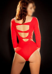 Escort Monica is wearing a red silk top and panties facing away from you
