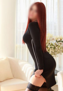 Escort Sylvia is wearing a tight black dress standing by the coutch